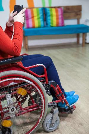 paraplegic: Irreconocible mujer discapacitada caucásica que se sienta en silla de ruedas y watchin mensaje con el teléfono inteligente, interior