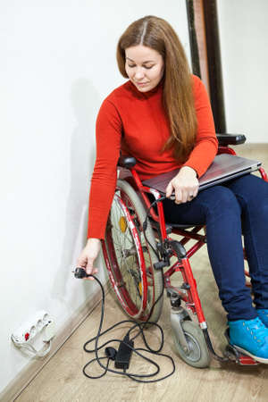 plug in: Smiling disabled woman sitting wheelchair with power plug in hand, trying to insert laptop plug into power outlet Stock Photo