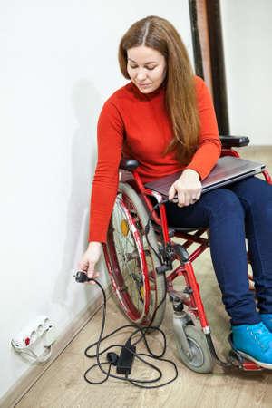 paraplegico: Sonriente mujer con discapacidad se sienta en silla de ruedas con el cable de alimentación en la mano, tratando de insertar el enchufe portátil en la toma de corriente