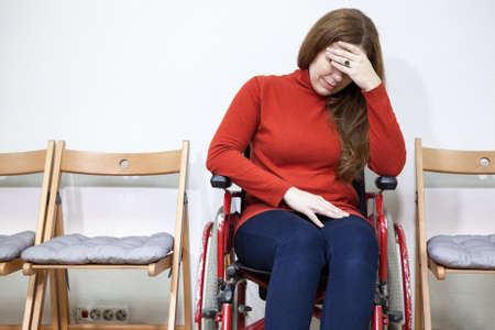 paralyzed: Paralyzed legs sad woman in invalid chair covers her face with hand while sitting indoors