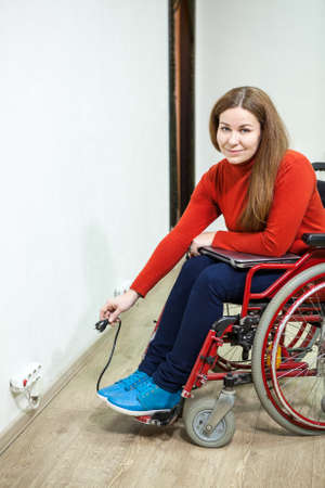 Happy and smiling disabled young woman holding laptop plug while sitting wheelchair indoors Stock Photo