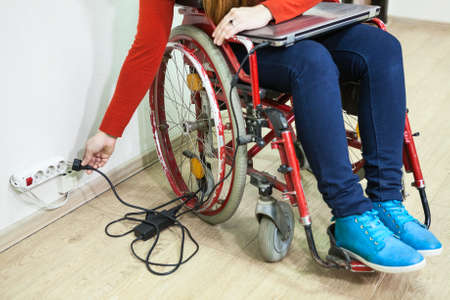 inconvenience: Unrecognizable woman inserting laptop plug with her hand in power socket, disabled person in wheelchair