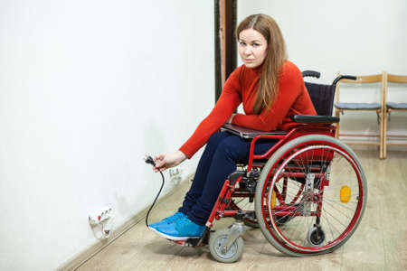 plug in: Disabled woman in invalid chair has some issues while inserting power plug into socket, looking at camera Stock Photo