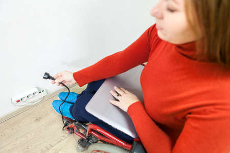 plug in: Disabled Caucasian woman in wheelchair trying to insert laptop plug into power socket