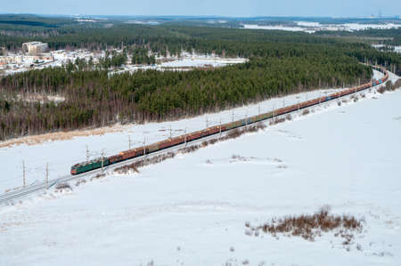 freight train: Long freight train passing through the winter evergreen woods, aerial view