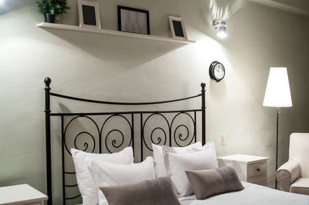 interior lighting: Bedroom interior details: bedside of forged steel bed with pillows. Lighting at evening