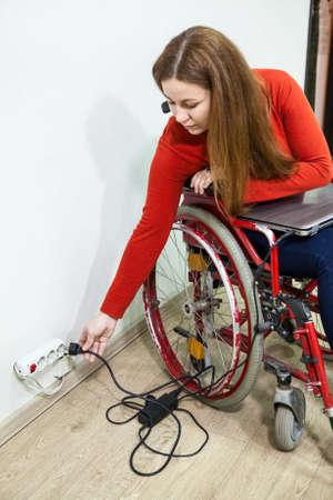 paraplegico: Sonriente mujer con discapacidad se sienta en silla de ruedas con la clavija de alimentación en la mano, que se extiende a la toma de corriente en la pared
