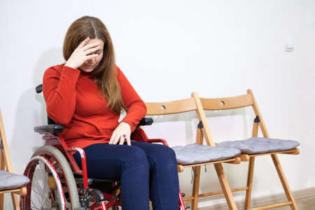 Disabled crying woman in wheelchair covers her face with hand while sitting between chairs