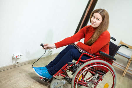 paralyzed: Paralyzed legs woman in invalid chair has some issues while inserting power plug into socket, looking at camera Stock Photo