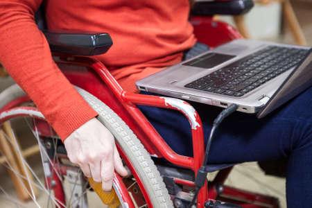 paraplegic: Ordenador port�til que pone en las rodillas de persona con discapacidad, que se sientan en silla de ruedas Foto de archivo