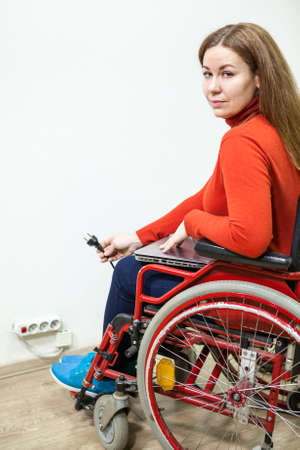 plug in: Disabled Caucasian woman sitting wheelchair with power plug in hand and looking at camera Stock Photo