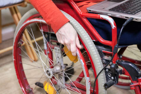 paraplegic: Hand of Caucasian disabled woman holding wheel, opened laptop laying on the knees Stock Photo