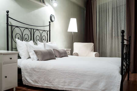 bedroom bed: Black forged bed with pillows and white linen is in dark bedroom at evening