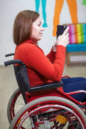wheel chair: Beautiful Caucasian disabled woman sitting wheel chair and typing message with smartphone, indoor