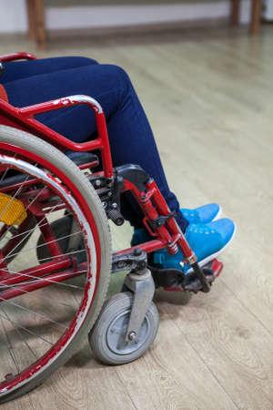 paraplegico: Piernas de la persona con discapacidad mientras que se sienta en silla de ruedas en la habitación doméstica