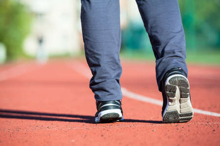 legs around: Athlete flexing his legs before jogging around the stadium, close-up view of feet in sport shoes