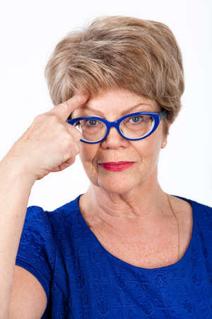 wrinkled brow: Facial portrait of senior woman in eyeglasses touching brow with forefinger, white background