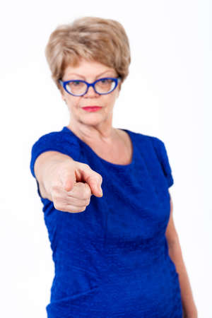 wrinkled: Defocused senior woman pointing with finger at you, looking at camera, white background Stock Photo