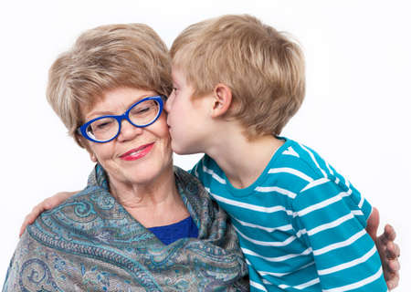 grandmother and grandson: Young grandson kissing joyful grandmother on the cheek, white background