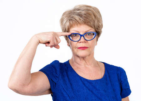 wearing: Senior Caucasian woman pointing with finger at the weared blue eyeglasses, white background