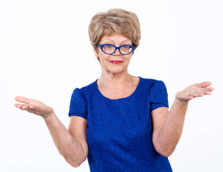 helpless: Senior smiling woman makes a helpless gesture, white background Stock Photo