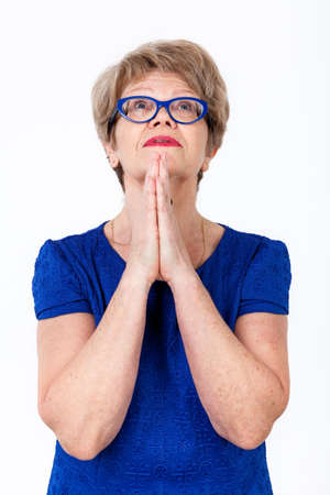 Portrait of elderly European woman praying with folded arms, looking up, white background Stock Photo