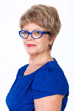 only women: Portrait of joyful senior Caucasian woman in blue eye-glasses and dress, white background