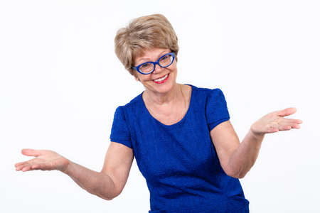 helpless: Laughing elderly European woman makes a helpless gesture, white background Stock Photo