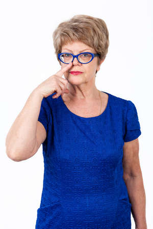 wrinkled: Half length portrait of senior Caucasian woman with eyeglasses pointing her nose with forefinger, isolated white background