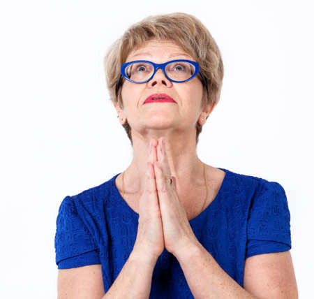 Pretty mature European woman praying, looking up, white background Stock Photo