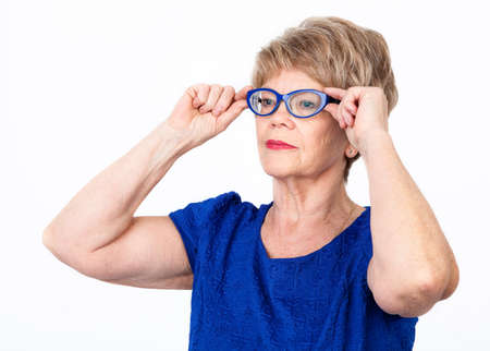 wrinkled: Mature Caucasian woman trying to wear new blue eyeglasses, holding with hands, white background