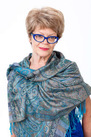 elderly woman: Elderly Caucasian woman portrait, blue spectacles, standing wrapped in shawl, white background