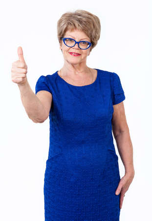 wrinkled: Happy senior woman weared blue dress showing thumb up gesture, white background