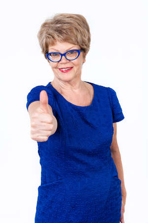 thumbs: Mature cheerful woman showing thumb up gesture to the camera, white background Stock Photo