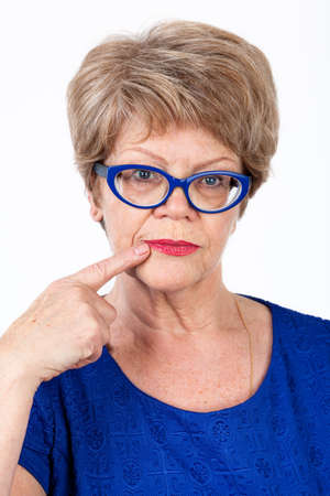 forefinger: Facial portrait of senior woman in eyeglasses touching her mouth with forefinger, white background