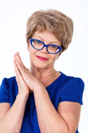 persona alegre: Mujer mayor caucásica alegre con las manos juntas mirando a la cámara, el fondo blanco Foto de archivo