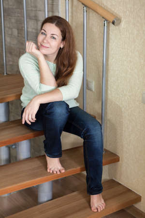 piedi nudi di bambine: bella donna allegra seduta sui gradini della scala in legno a casa con i piedi nudi