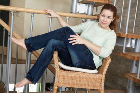 legs folded: Jeans weared pretty woman sitting in rattan chair, legs folded, indoor Stock Photo