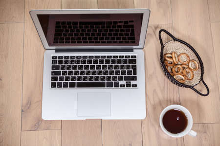 trompo de madera: Modern laptop, cup of cofee and snacks are on the wooden floor, view above