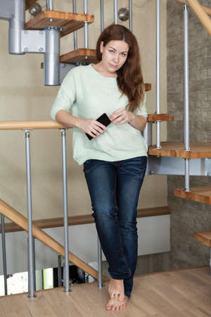 full lenght: Caucasian beautiful barefoot woman holding hands mobile phone, domestic room, full lenght