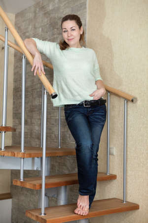 jean: Young woman dressed in jeans and with bare feet standing on spiral staircase at home Stock Photo