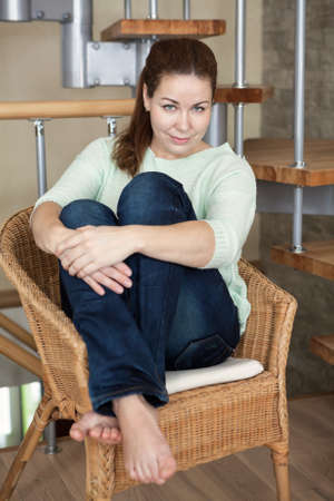 young girl barefoot: Young Caucasian barefoot woman sitting in a wicker chair with knees wrapped around with hands Stock Photo