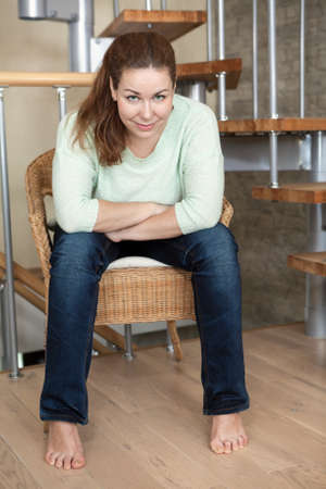 leaning forward: Caucasian woman sitting in chair, her hands folded on her knees, leaning forward Stock Photo