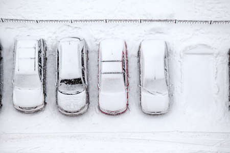covered in snow: Free parking place is in line of vehicles, winter time, view from above Stock Photo