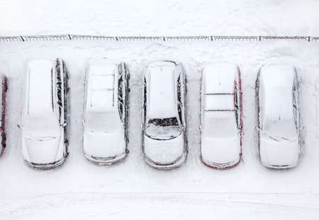 lot of: Car standing at winter parking lot covering with snow, top view Stock Photo