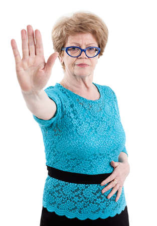one senior woman only: Woman retirement age stretching out her hand, gesturing stop sign, palm forward, isolated on white background