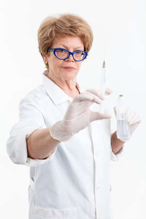 healthcare worker: Senior woman healthcare worker looking at syringe for vaccination in her hand, white background