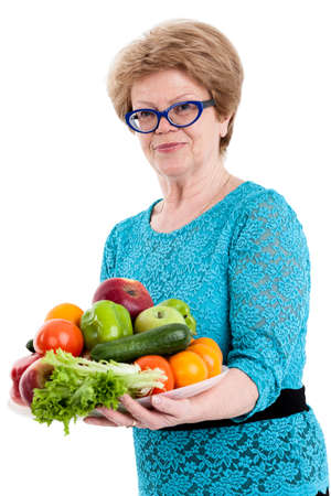 eating fruits: Mature happy woman holding a tray with fruits and vegetables in hands, isolated white background Stock Photo