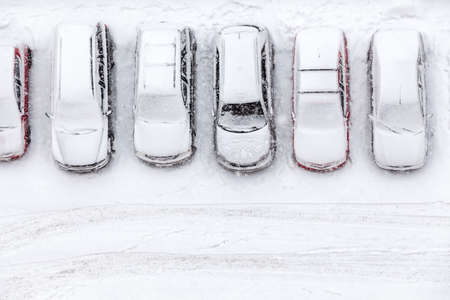 Vehicles standing at winter parking lot covering with snow, top view, copyspace Stockfoto