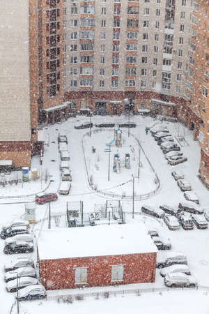 dwelling: Strong snowfall is in dwelling building courtyard, cars parking lot under snow, winter season Stock Photo